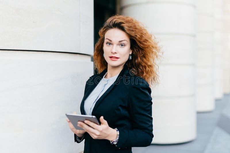 Donna adorabile con capelli ricci che portano vestito nero e blusa bianca, tenenti il computer della compressa, i messaggi di bat fotografia stock