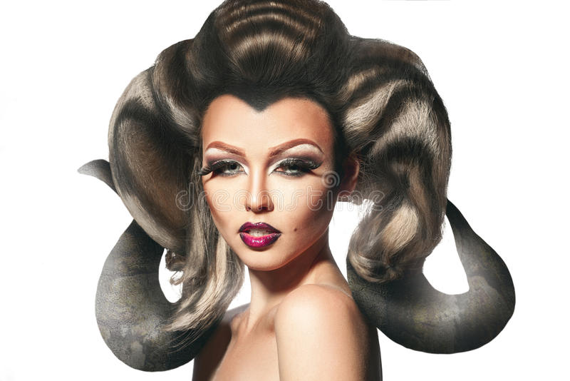 Donna adorabile del diavolo con i corni in testa che distoglie lo sguardo nello studio fotografia stock