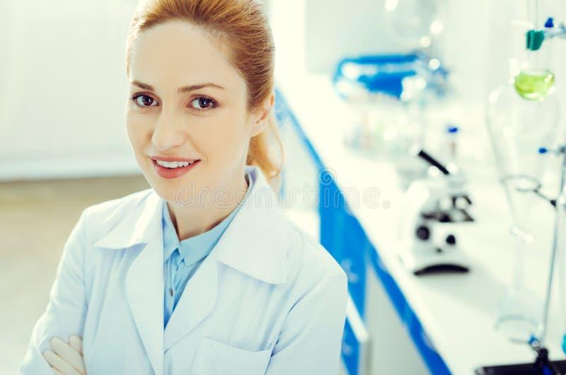 Donna adulta allegra che sorride mentre esaminando macchina fotografica in laboratorio fotografie stock libere da diritti