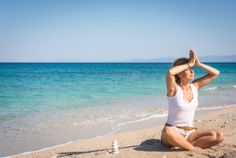 Donna adulta che medita su spiaggia nella pace, di mattina fotografia stock