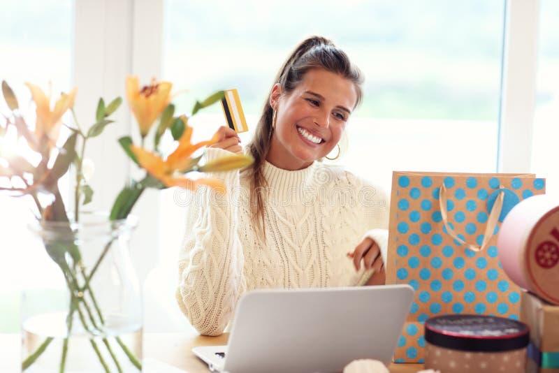 Donna adulta che porta maglione caldo e che shoping online fotografie stock