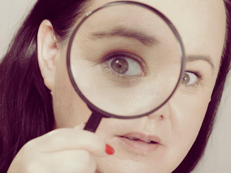 Donna adulta con la lente d'ingrandimento fotografia stock libera da diritti