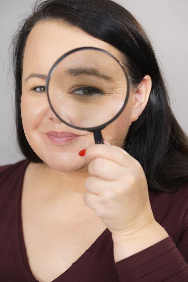 Donna adulta con la lente d'ingrandimento fotografia stock