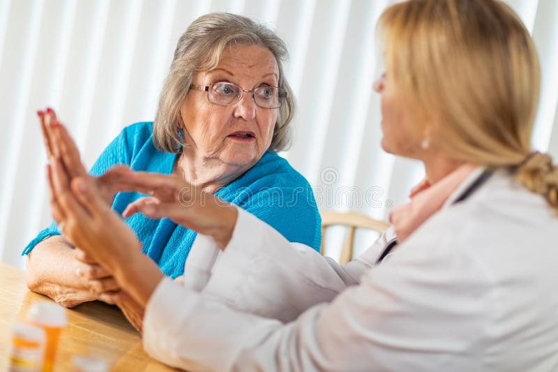 Donna adulta senior confusa che parla con medico circa la terapia della mano immagine stock