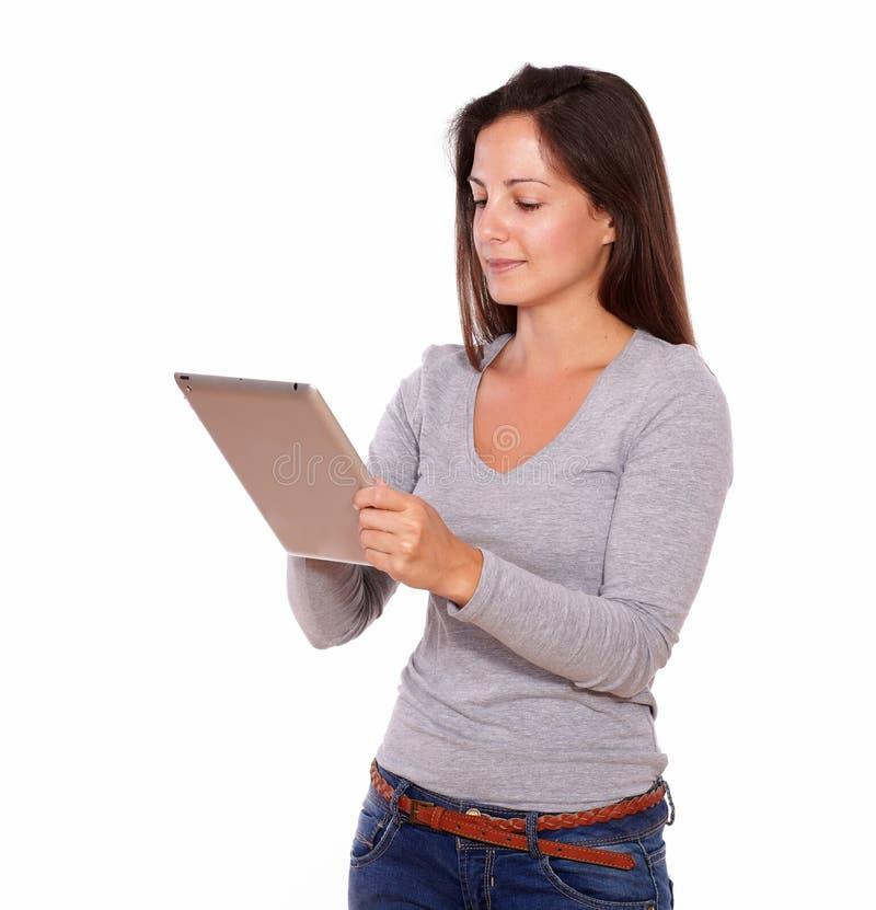 Donna affascinante che lavora al pc della compressa mentre stando fotografia stock libera da diritti