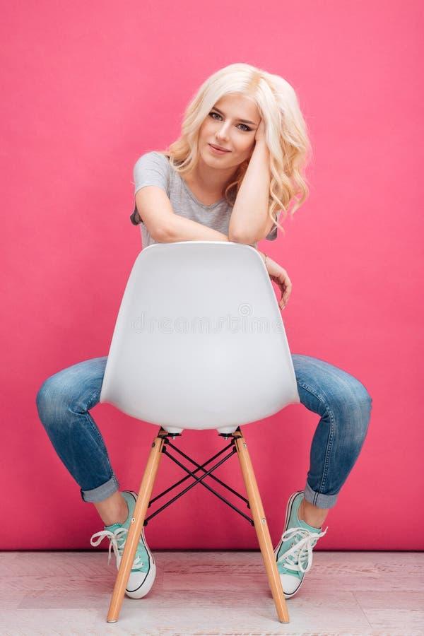 Donna affascinante che si siede sulla sedia e che esamina macchina fotografica fotografie stock libere da diritti