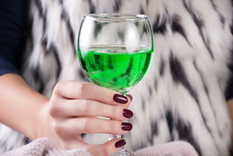 Donna affascinante che tiene la bevanda verde dell'assenzio disponibile fotografia stock libera da diritti