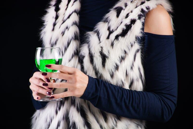 Donna affascinante con la bevanda verde dell'assenzio immagine stock