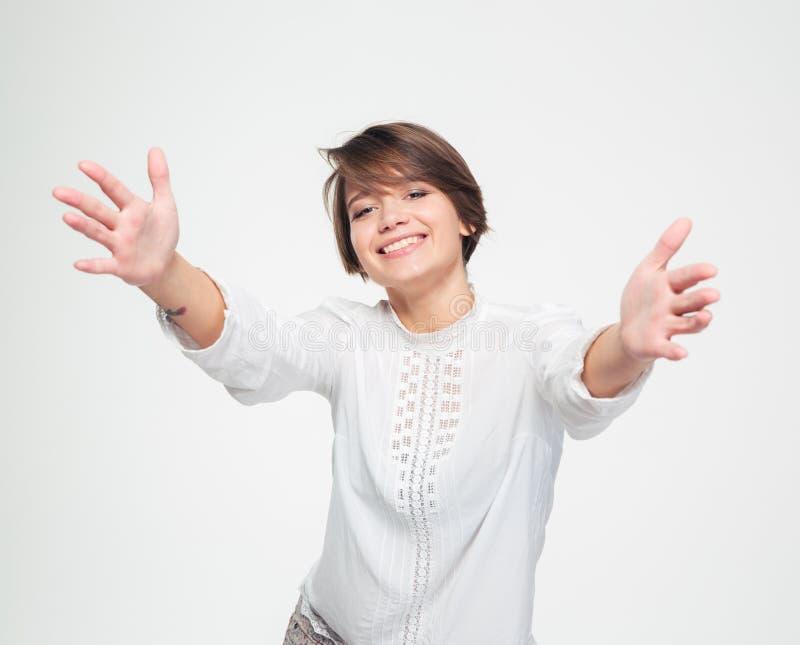 Donna affascinante felice con le mani aperte che raggiungono verso la macchina fotografica immagine stock libera da diritti