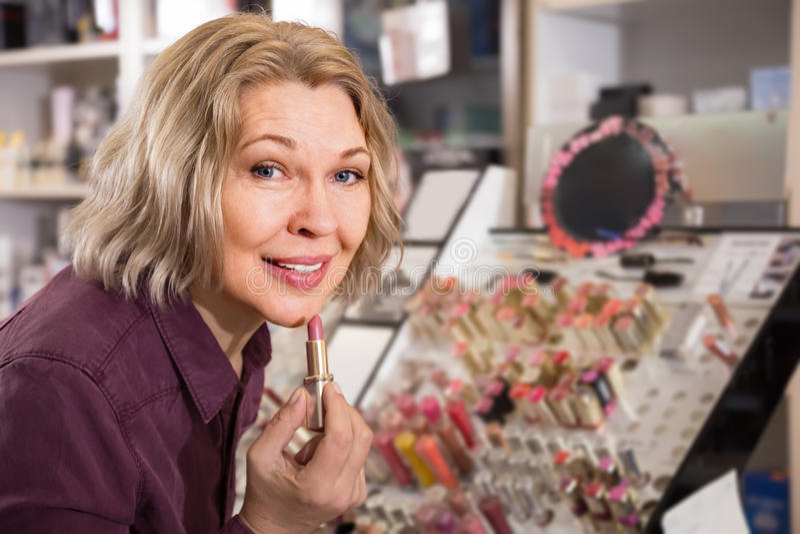 Donna affascinante matura che sceglie labbro più grassoccio su esposizione fotografie stock