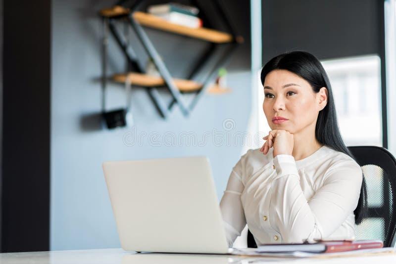 Donna affascinante seria che lavora nell'ufficio fotografia stock