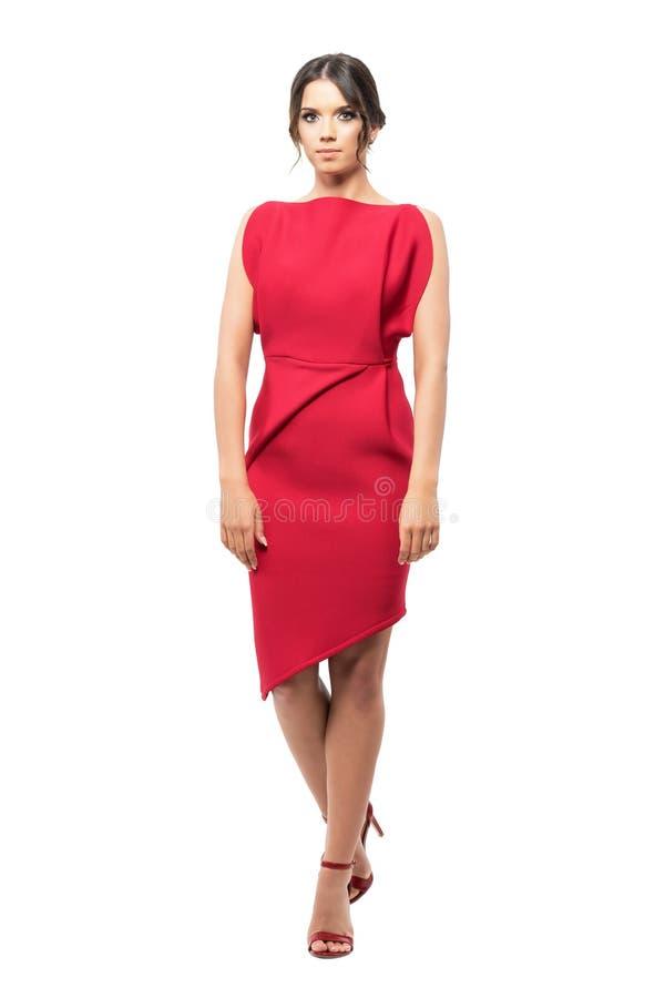 Donna affascinante in vestito da sera rosso che sta con le gambe attraversate fotografia stock libera da diritti