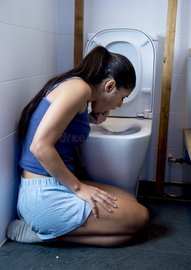 Donna affetta da bulimia che ritiene le dita colpevoli malate in bocca che vomita e che getta su nella toilette del WC fotografie stock