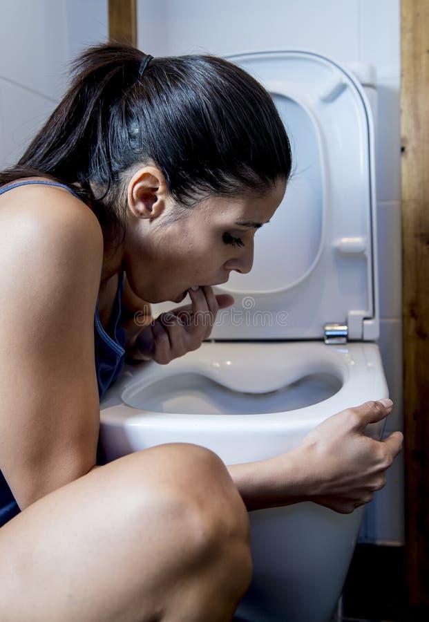 Donna affetta da bulimia che ritiene le dita colpevoli malate in bocca che vomita e che getta su nella toilette del WC fotografia stock