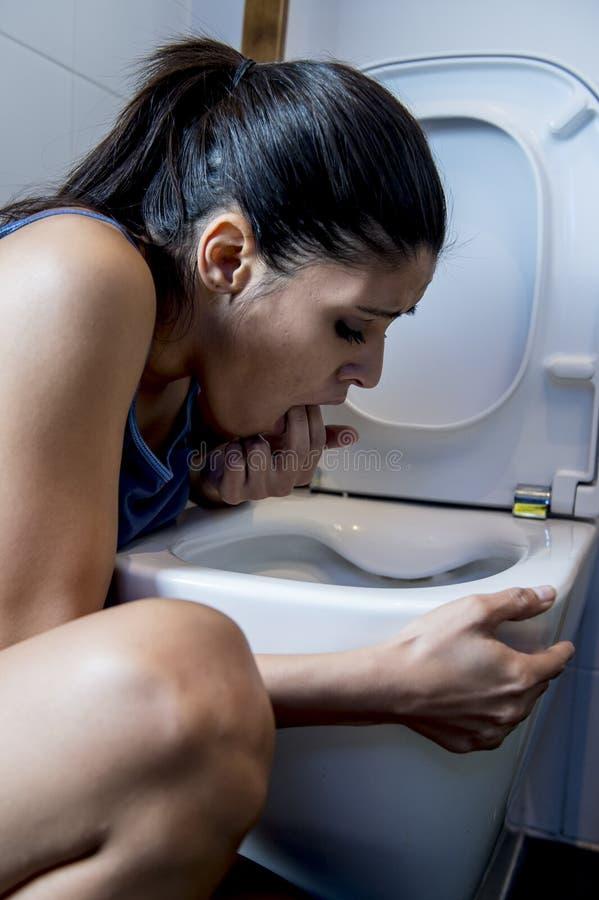 Donna affetta da bulimia che ritiene le dita colpevoli malate in bocca che vomita e che getta su nella toilette del WC fotografia stock libera da diritti