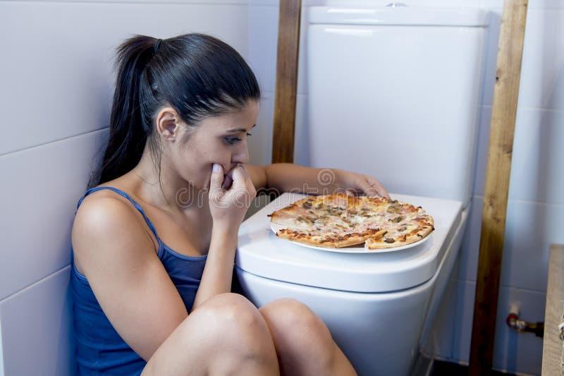 Donna affetta da bulimia che ritiene seduta colpevole malata al pavimento della toilette che si appoggia WC che mangia pizza fotografie stock