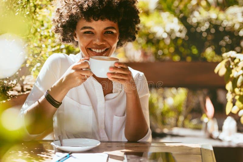 Donna africana allegra che mangia caffè fotografia stock
