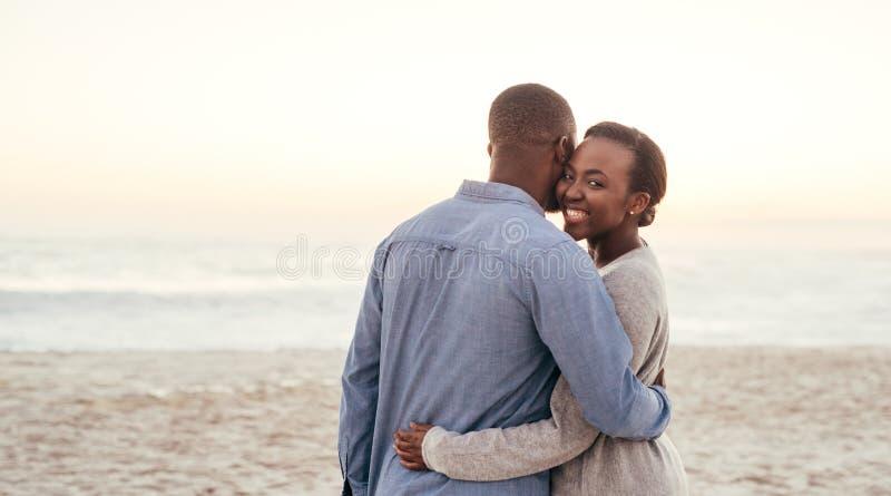 Donna africana che abbraccia il suo ragazzo su una spiaggia al tramonto fotografia stock