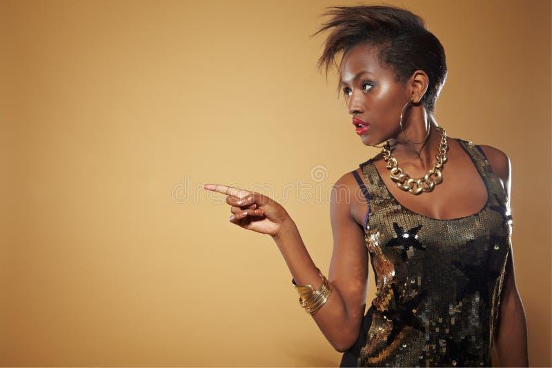 Donna africana che indica con la barretta immagini stock