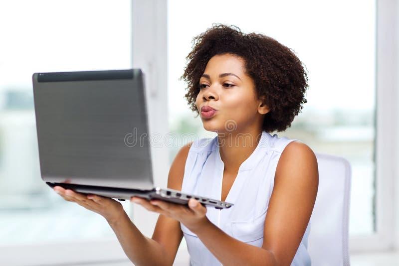 Donna africana che invia bacio al computer portatile fotografia stock libera da diritti