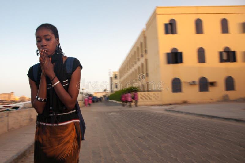 Donna africana che prega nella via del Saint Louis immagine stock libera da diritti