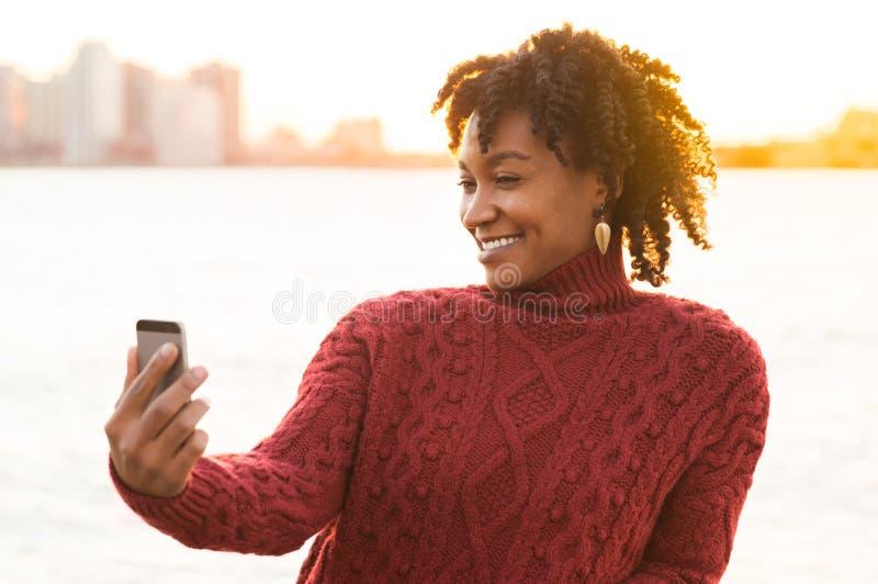 Donna africana che prende selfie immagine stock