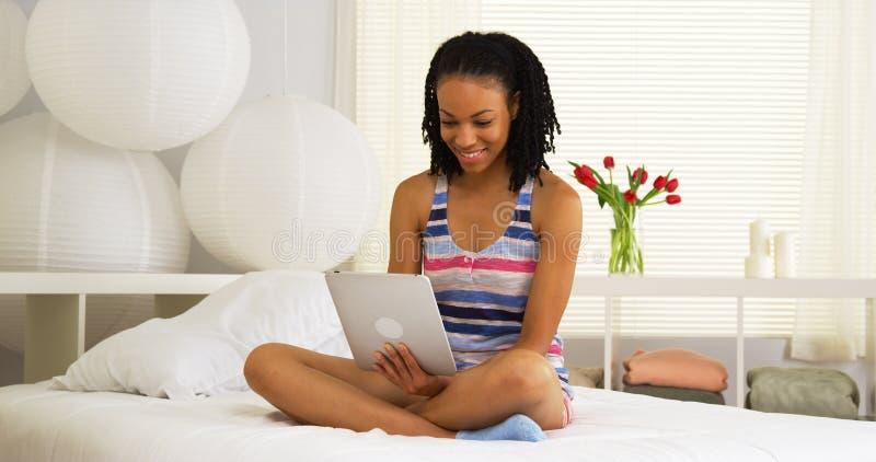Donna africana che si siede sul letto facendo uso della compressa fotografie stock libere da diritti