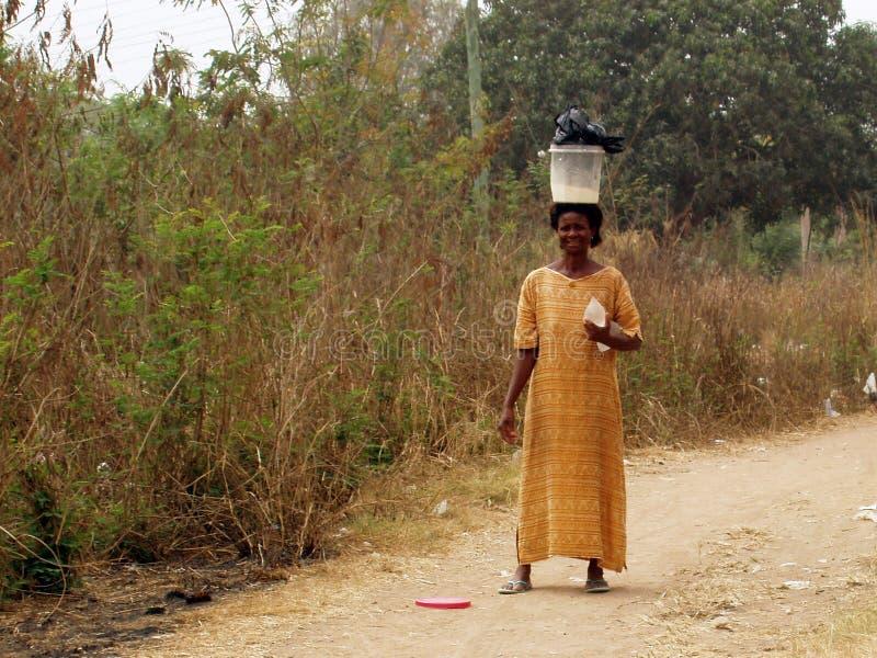 Donna africana con la benna sulla testa fotografie stock