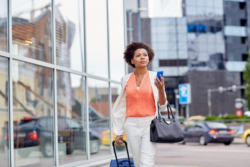 Donna africana con la borsa e lo smartphone di viaggio immagine stock libera da diritti