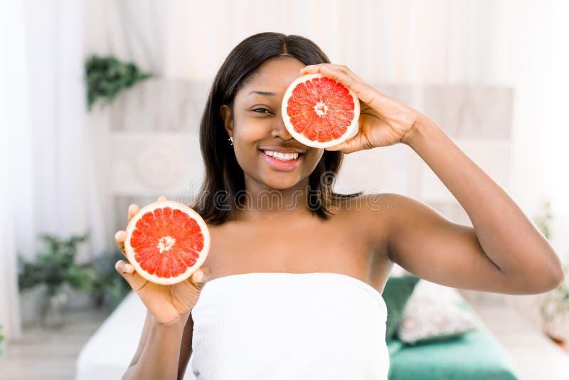 Donna africana di bellezza con il pompelmo arancio dell'agrume con l'ente sano della pelle Vitamina fresca attraente Colpo dello  immagine stock libera da diritti