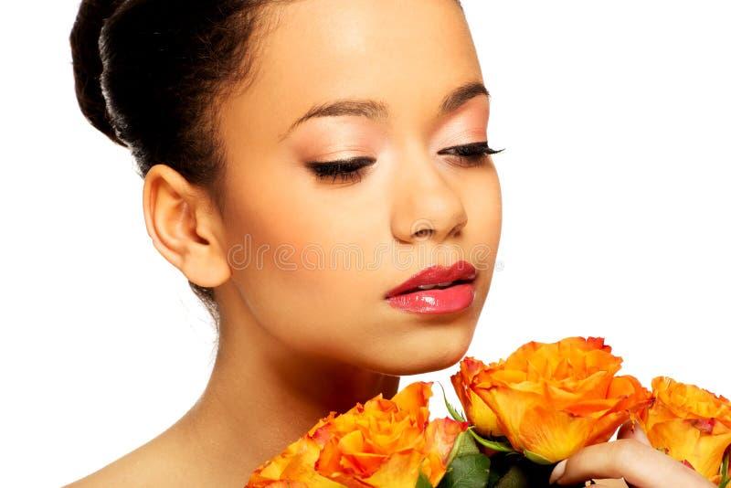 Donna africana di bellezza con le rose fotografia stock
