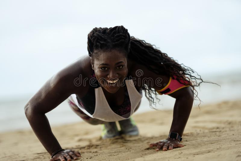 donna africana di forma fisica di Spinta-UPS che fa i piegamenti sulle braccia fuori sulla spiaggia fotografia stock libera da diritti
