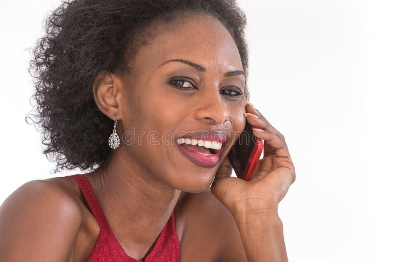 donna africana felice che convince il suoi telefono cellulare e sorridere immagini stock libere da diritti