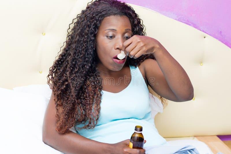 Donna africana malata che beve la sua medicina a letto fotografie stock libere da diritti