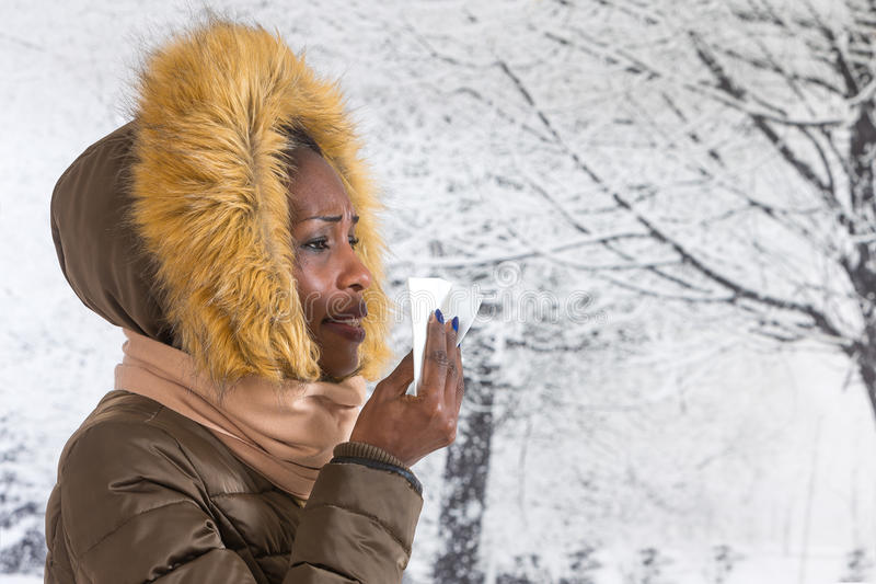 Donna africana malata del ritratto del primo piano giovane con il cappotto incappucciato con pelliccia, fondo di inverno del naso immagini stock libere da diritti