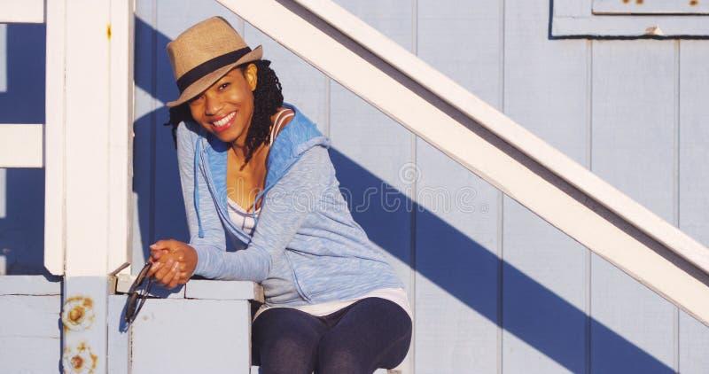 Donna africana sveglia che si siede all'aperto fotografie stock libere da diritti