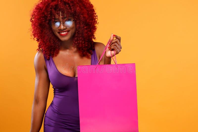 Donna afroamericana ad acquisto che tiene borsa rosa su fondo arancio sulla festa nera di venerdì Copi lo spazio per fotografie stock