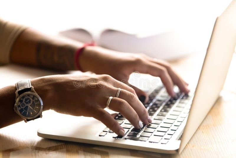 Donna afroamericana che per mezzo del computer portatile, scrivente sulla tastiera, u vicina immagini stock libere da diritti