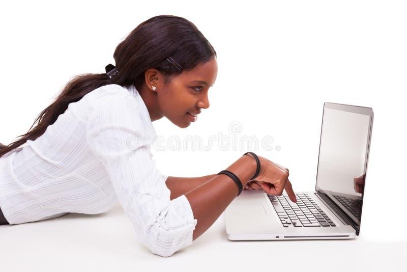 Donna afroamericana che per mezzo di un computer portatile - persone di colore immagine stock