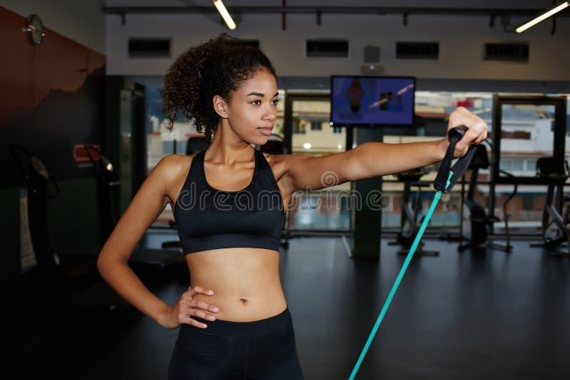 Donna afroamericana che si esercita con l'estensore di forma fisica alla palestra immagini stock libere da diritti