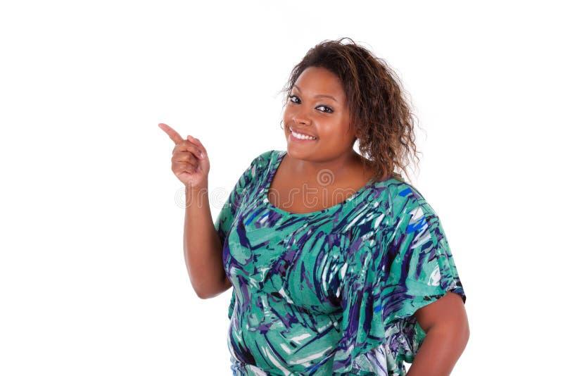 Donna afroamericana che sorride indicando qualcosa - persone di colore fotografie stock