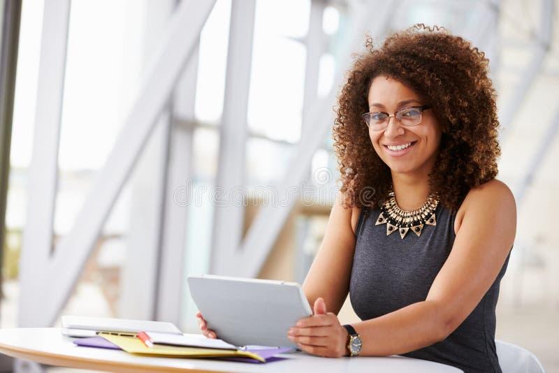 Donna afroamericana con la compressa, sorridente alla macchina fotografica immagini stock