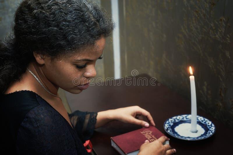 Donna afroamericana da pregare a casa nella sera fotografia stock libera da diritti