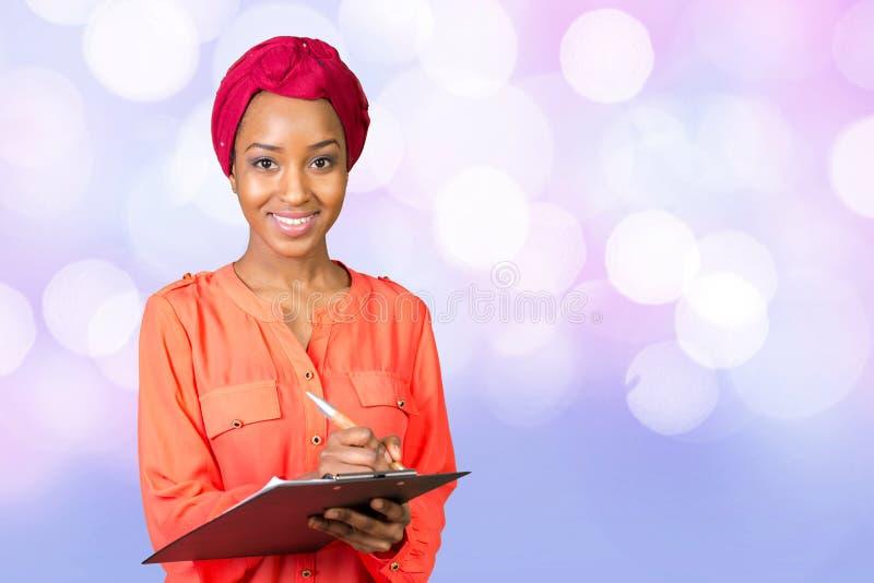 Donna afroamericana di affari con la lavagna per appunti immagine stock libera da diritti