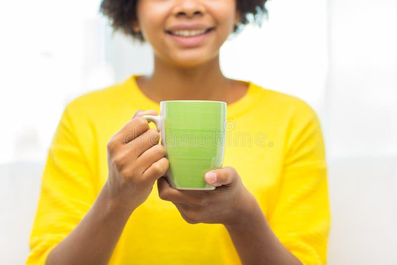 Donna afroamericana felice che beve dalla tazza di tè fotografie stock libere da diritti