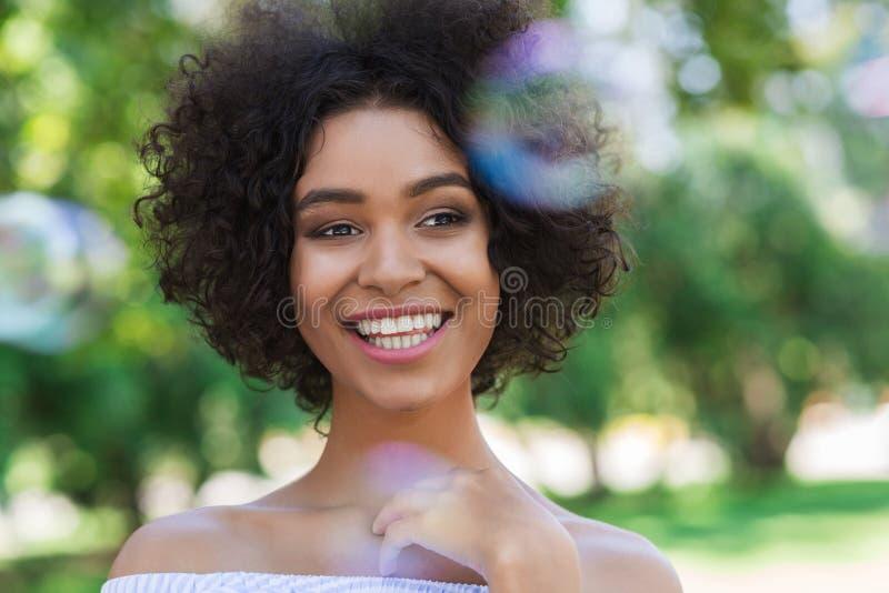 Donna afroamericana felice circondata dalle bolle in parco fotografia stock libera da diritti