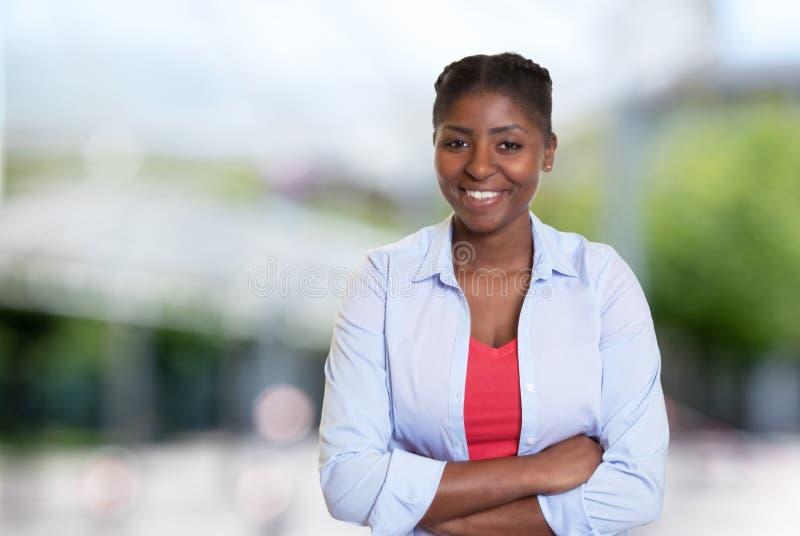 Donna afroamericana giovane di risata con l'abbigliamento casual immagine stock