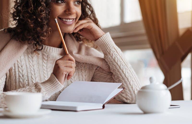 Donna afroamericana positiva che fa le note nel caffè fotografie stock