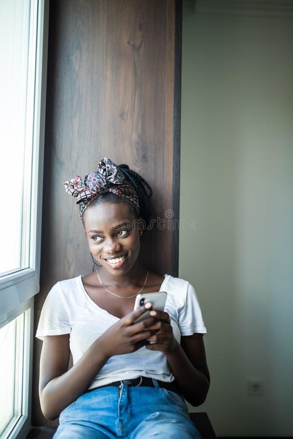 Donna afroamericana sorridente che si siede sul davanzale e che scrive messaggio sullo smartphone a casa immagini stock libere da diritti