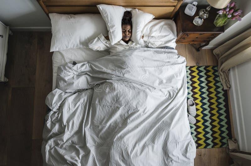 Donna afroamericana su insonnia del letto e sul concetto dell'inquinamento acustico immagini stock libere da diritti